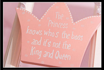 Pink and white painted, wooden princess crown saying The Princess Knows Who's the Boss and It's Not the King and Queen