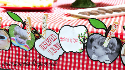 Apple of My Eye baby shower party banner with apple shaped photo cut outs with pictures of the kids draped on the dessert table
