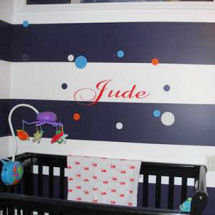 Red baby name decal letters on black and white painted horizontal stripes in a Beatles theme baby nursery