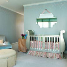 A baby nursery with blue wall paint color, pink flowered ceiling border and metallic silver painted sleigh crib for a girl