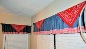 Baby boy western cowboy nursery window valance. Rustic blue denim curtains with a red gingham check border.