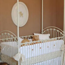 Tan vintage baby girl nursery with iron crib antique bedding set and silhouette wall decorations