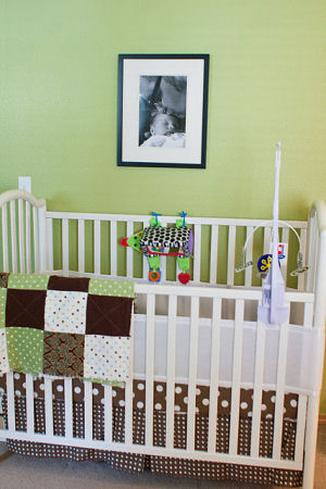 Green, brown and white polka dot baby crib with breathable bumper and educational crib mobile