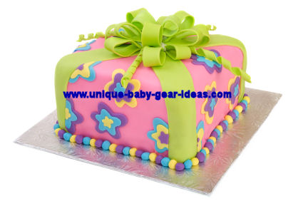 Lime green and purple girl baby shower or birthday party cake with fondant flowers topped with a large bow made of fondant ribbons.