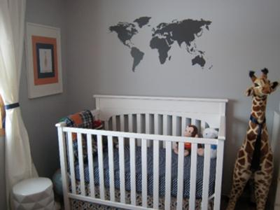 Baby boy gray and orange nursery with world map wall decorations.