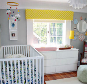 Gray and yellow baby nursery with bright accent colors and white trim.