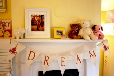 White wooden mantelpiece in Hadley's room decorated with DREAM bunting banner, framed artwork and stuffed toys