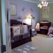 Lavender nursery wall paint with green and brown butterfly baby bedding, area rug and crib mobile