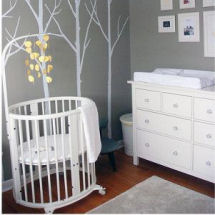 Modern gray and white baby boy nursery with white crib and tree with bare limbs wall decal and mobile