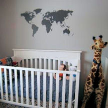 Modern gray and white world map baby nursery room with large stuffed toy giraffe