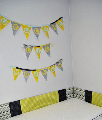 Charming gray, yellow and white felt wall banner made for a baby shower now decorates the wall of the nursery