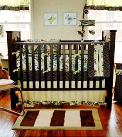 Green and chocolate brown paisley baby crib bedding set in a nature nursery theme with a tree wall mural created with a large decal