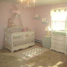 Pink and white princess nursery decorated with a crib crown and elegant crystal chandelier