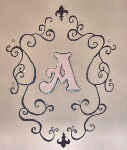 Hand painted black scrollwork and fleur de lis graphics painted on our princess' pink nursery wall framing her monogram, the letter A.