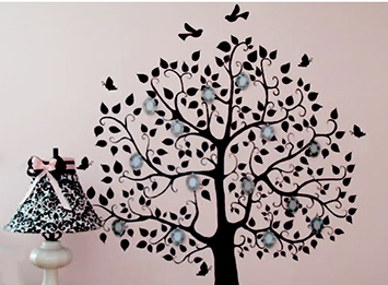 Hand painted family tree nursery wall art on a pink painted wall in a baby girl's room.