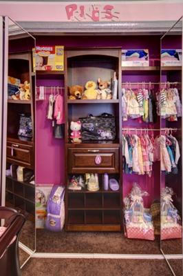 Closet organizer system in a pink princess theme baby nursery closet