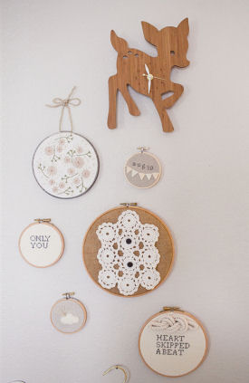 A cluster of embroidery hoops including a mini-hoop with baby's birth date arranged on the nursery walls