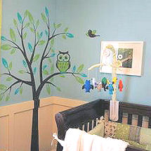 Large baby owl themed tree nursery wall decal applied over wooden trim in a corner by the crib