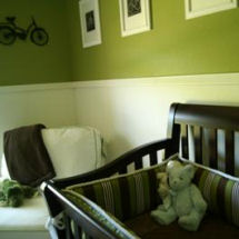 Vintage olive green and antique white unisex neutral baby nursery theme with a black crib, teddy bear and bicycle art