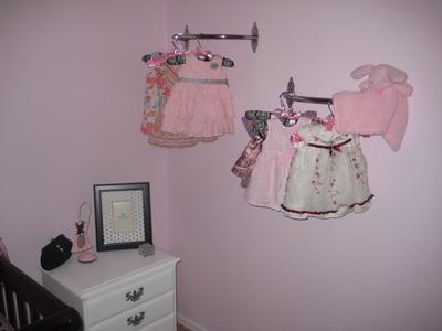 Ava's pretty dresses hung on custom made clothes racks make a pretty display on the nursery wall