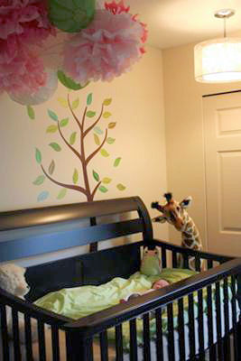 Ava's garden nursery with her giant, toy giraffe watching over our baby girl sleeping in her crib.