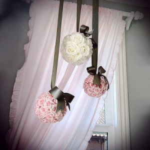 Pink silk rose balls hung by a chocolate brown satin ribbon