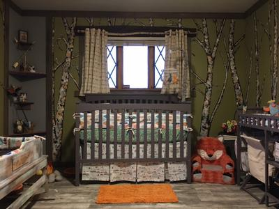 View of the baby's crib in Arrow's forest nursery theme