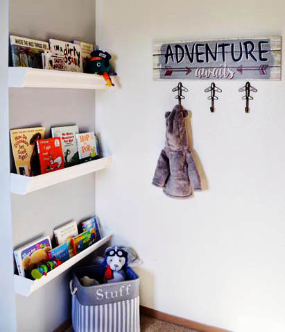 DIY rain gutter nursery wall book shelves in a baby boy nursery reading nook corner.