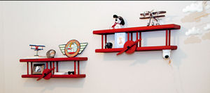 Red airplane wall shelves in a baby boy airplane nursery theme