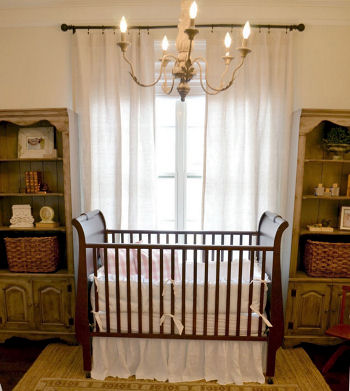 Vintage baby girl nursery decorated in pink and neutral colors with a sleigh crib and classic white crib bedding set