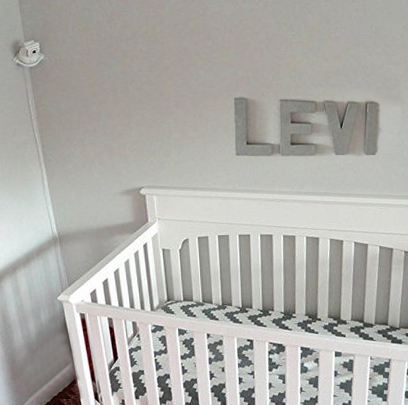 Corner shelf for a baby monitor in a neutral nursery.