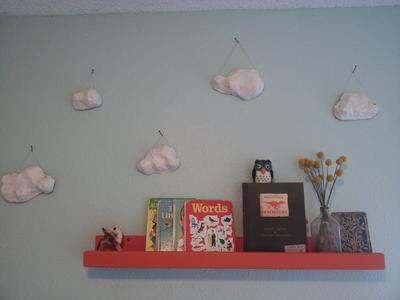 Orange wooden display shelf made by dad with paper mache clouds
