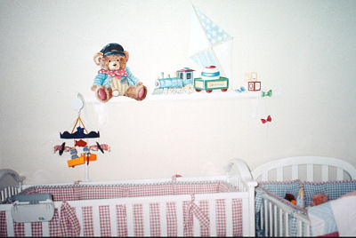 A teddy bear choo choo train theme nursery wall mural painted and designed <br>by Lisa Desantis-Kirchmer of Art of Walls Inc. in a baby boy nursery room with red and white and blue and white gingham baby crib bedding sets.