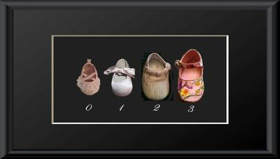 Preserved baby shoes in a growth chart shadow box picture frame