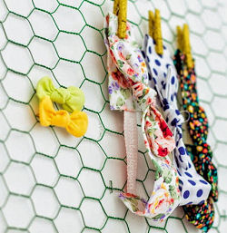 A DIY nursery wall letter made from painted chicken wire doubles as Willow's headband and bow holder
