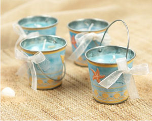 Beach theme sand buckets are candle pails decorated with ribbons and shells used as baby shower favors