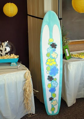 A surfboard decorated with hibiscus flowers added to the beach theme baby shower decorations