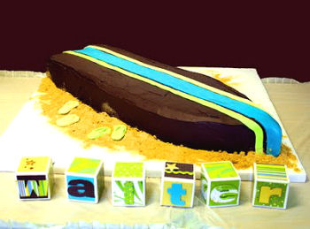Chocolate surfboard shaped beach theme baby shower cake with ganache frosting and buttercream filling