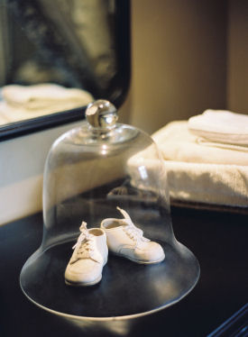 Vintage baby shoes on display in the nursery protected under a glass dome