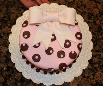Cute round pink and brown girl baby shower cake decorated with pink and brown fondant polka dots and a light pink gum paste bow