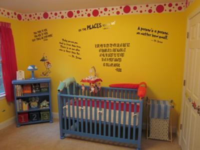 Our favorite Dr Seuss quotes and red and white wallpaper border decorate the wall above the baby's crib