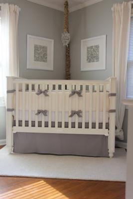 A creamy ivory and light gray crib bedding set in a masculine, baby boy nursery with touches of burlap and woven storage baskets.