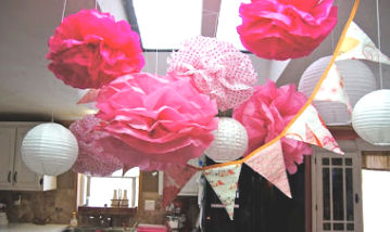 Hot pink and white tissue paper pom poms and party banner decorations for a baby girl shower