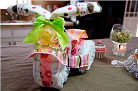 Tricycle diaper cake for a baby girl butterfly theme baby shower with ribbons bows baby bottles and 50 disposable diapers