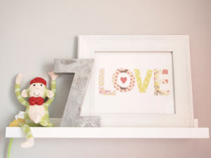 neutral gray nursery wall letter frame ledge arrangement