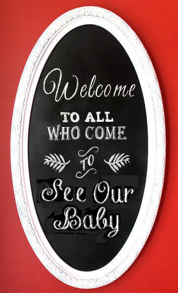 DIY chalkboard welcome sign in an oval frame for a baby nursery room