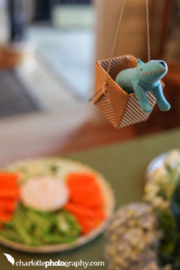 Colorful toy animals fill the baskets of the homemade hot air balloons decorating the area over the food table at the baby shower
