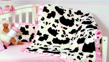 cow print baby crib bedding set for a girl nursery in pink black and white