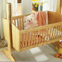 Heirloom wood pendulum baby cradle with classic lines made from ash wood