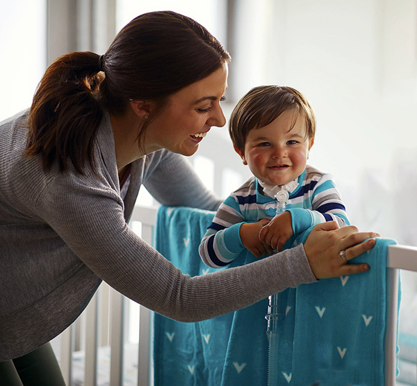 Sturdy baby crib mattress with baby standing up in crib.